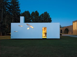 Seen from the outside, angular slits offer tantalizing glimpses of the home's interior.
