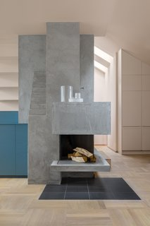 To inform the color palette for this interior renovation in Stockholm, NOTE Design Studio began with three inspirational images. The sculptural fireplace, covered in plaster, contrasts with oak parquet floors.