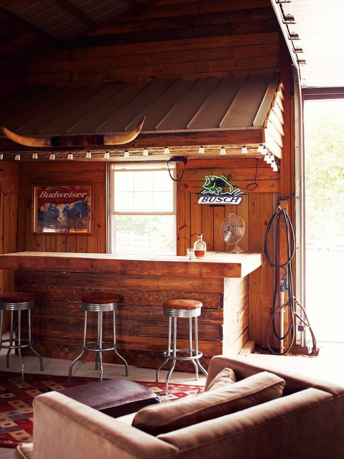 Dining Room, Bar, Chair, Stools, Rug Floor, and Ceiling Lighting Inside, Paul often dispenses whiskey to friends from behind the rustic bar.  Photo 6 of 10 in A Modern Farmhouse Recalls Old-Time Americana