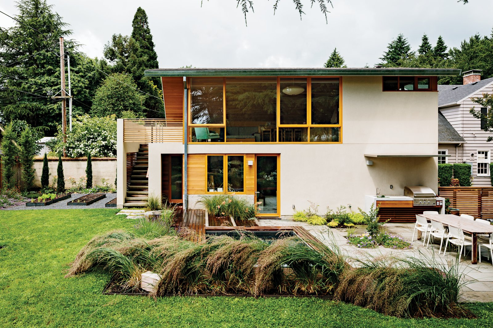 Outdoor, Grass, Small Patio, Porch, Deck, Concrete Patio, Porch, Deck, Back Yard, Gardens, Shrubs, and Trees Fusion Landscape Design worked with PATH to remake the backyard into a grown-up playground. Under the stairwell sits a tiny custom cedar sauna and an outdoor shower—just a literal hop, skip, and jump away from the sprawling in-ground eight-by-ten-foot hot tub. Down three short stairs, Gloster's Elan dining table from Design Within Reach is surrounded by Spark chairs by Don Chadwick for Knoll and a built-in fire pit and DCS grill by Fisher & Paykel—all resting on a smooth surface of bluestone pavers.  Photo 10 of 10 in Salvaged Wood Renovation in Portland