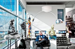 A longtime collector of furniture and art, Dr. Robert Geller finally lives among his prized possessions. In the living room, he sits on a Barcelona chair by Mies van der Rohe for Knoll. To his right are an Arco floor lamp by Achille and Pier Giacomo Castiglioni for Flos and a BeoLab 5 speaker from Bang & Olufsen. The sculptures to Geller's left and in the foreground are by American artist Arlene Shechet, Everything Seems to be Something Else and Just Remembered.