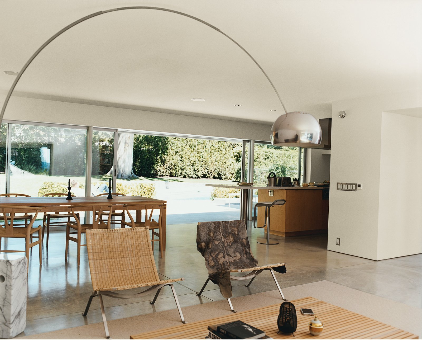 Dining Room, Chair, Table, Floor Lighting, and Concrete Floor A 14-foot-wide opening at the rear of the house contributes, along with the concrete flooring, to an almost seamless transition from indoors to the patio. A spate of mid-century furnishings includes chairs by Hans Wegner and Poul Kjærholm and an Achille Castiglioni Arco lamp.  Photo 2 of 13 in On the Level