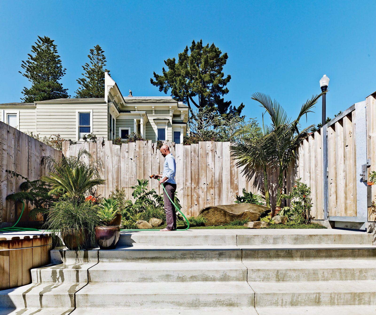 Outdoor, Vertical Fences, Wall, Small Patio, Porch, Deck, Concrete Patio, Porch, Deck, and Grass Russell-Clarke tends a small garden.  Photo 4 of 17 in Striking Slatted Wood and Glass Home in San Francisco