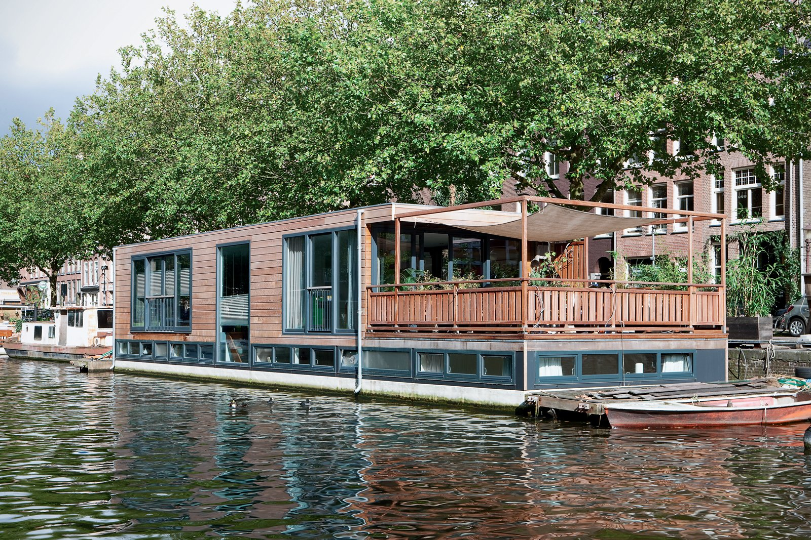 Exterior, Flat RoofLine, Boathouse Building Type, and Wood Siding Material The couple plan to add a kitchen garden to the platform just below the terrace that connects to the kitchen.  Photo 4 of 4 in A Live-In Kitchen on a Houseboat in Amsterdam