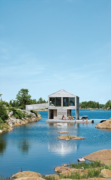 """Exterior and Cabin Building Type Cedar slats mark the facade of Floating House, Doug and Becca Worple's lake house in Ontario. The architects, MOS, chose materials and shapes that wouldn't stand out. """"They're really simple, almost Platonic forms,"""" principal Michael Meredith says. The modest cabin has boat, a gabled roof and a cladding of untreated cedar, a material that shows up on docks and homes along Georgian Bay. """"Allowing the buildings to weather seems the right thing to do,"""" Sample says. And it's ready for winter: Sliding barn doors seal the place up as an impenetrable box.  Photo 79 of 101 in 101 Best Modern Cabins"""