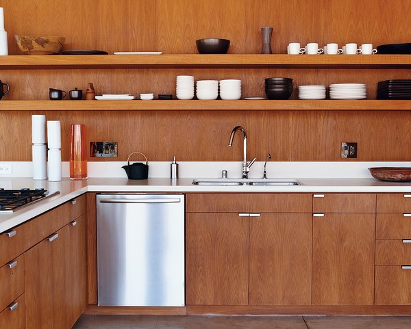 Kitchen, Wood Cabinet, Dishwasher, and Undermount Sink The kitchen cabinetry, custom designed by the architects, is smooth brown teak. The faucet is by Hansgrohe, and the dishwasher is by Bosch.  Photo 3 of 14 in Inspired Indoor Teak Looks from Desert Utopia