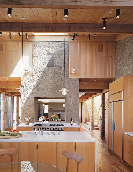 """The house has the feel of a refined barn: The kitchen flows into the dining area, then into a den. The two PISE """"chimneys"""" serve to demarcate the transitions and visually unite the space.  Photo 2 of 4 in PISE Does It"""