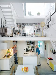 Three thin slabs have been staggered vertically through the space to create three distinct floors and allow light to flood in from the front, back, and roof. The white Saari kitchen makes the most of a compact space.