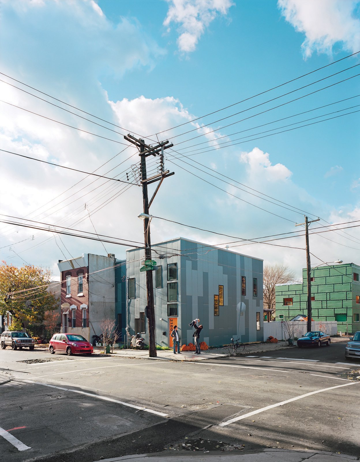 The HardiePanel siding on the adjacent 100K and 120K houses is a dramatic break from East Kensington's mostly brick facades. The simple, well insulated box and the absence of a third floor keep each house affordable, sustainable, and within the reach of young families.  Photo 6 of 11 in Green Urban Housing in Philadelphia