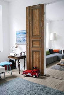 The goal of the renovation was to get the most out of every square inch, since there was no way to expand beyond the apartment's historic envelope. Always-open double doors—stripped down to their original wood—connect the railroad-style parlors to create an open, loftlike feel.