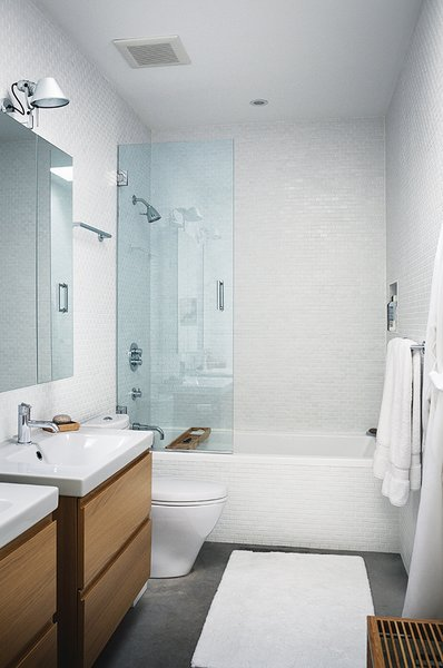 In the master bathroom, Godmorgon vanities from Ikea stand next to a dual-flush Aquia toilet from Toto. A Tolomeo Wall Spot lamp, designed by Michele De Lucchi and Giancarlo Fassina for Artemide, hangs above the mirror.  Photo 6 of 11 in Modern Lakeside Retreat Stripped Down to the Basics