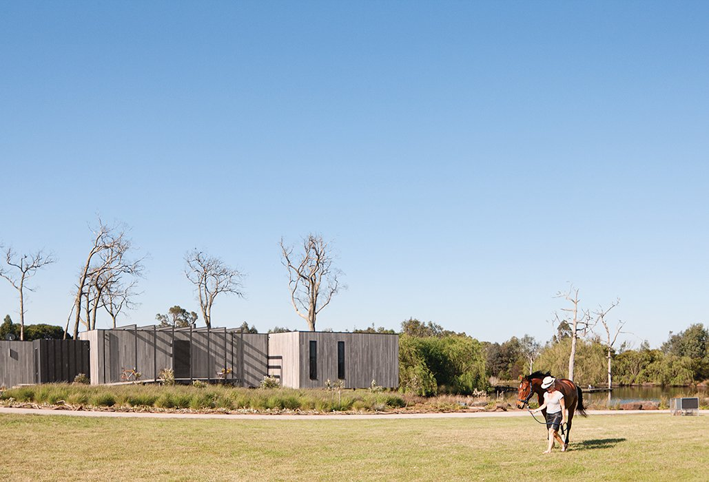Exterior, Flat RoofLine, House Building Type, and Wood Siding Material The 16-acre property includes room for the family's horses and a portable chicken coop.  Photo 6 of 8 in Living Simply on a Lush Australian Estate