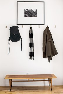 Inside the front door, coats hang from aluminum Bjärnum hooks by Ikea above a vintage Lane coffee table, which Magill bought from a coworker, and beneath a photograph by Beth Mercer.