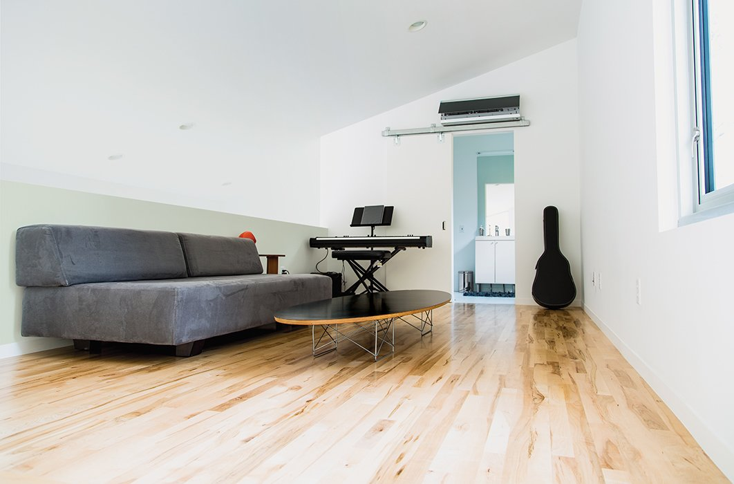 Living Room, Ceiling Lighting, Coffee Tables, Recessed Lighting, Sofa, and Light Hardwood Floor The loft is furnished with a Tillary sofa from West Elm and a wire-base Elliptical table by Charles and Ray Eames.  Photo 5 of 12 in A Versatile House Fulfills All This Musician's Needs