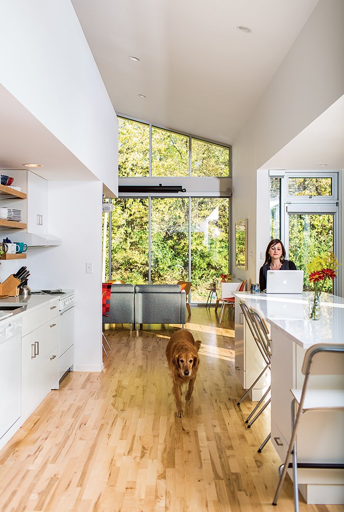 Kitchen, White Cabinet, and Light Hardwood Floor Sarah Magill and Copa, her golden retriever, relax in the kitchen of her home in Kansas City, where an eco-quartz-topped island can be used as a dining table—one of the home's many adaptable features. The Akurum cabinets and handles are from Ikea, as are the Franklin folding bar stools, and the appliances are compact models from Summit.  Photo 8 of 12 in A Versatile House Fulfills All This Musician's Needs