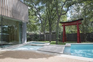 """During Webber + Studio's renovation and expansion of a midcentury home, the architects sought to imbue a sense of """"wabi-sabi,"""" or imperfection in beauty, with an irregularly shaped pool and dappled light that's provided by a nearby tree. Large stepping stones and a garden gate also reference Japanese elements."""