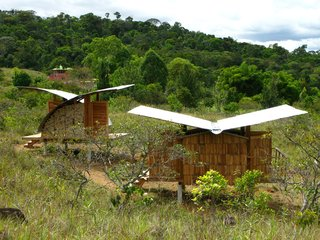Two housing models perch lightly in a field, both featuring gently curved, rainwater-catching butterfly roofloines.