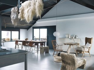 Leen and Middendorp's living space is peppered with an assortment of objects and textures, including sheep's wool, an antique French farmhouse table, salvaged chairs, a Glo-Ball light by Jasper Morrison for Flos, and an Axel leather sofa by Gijs Papavoine for Montis.