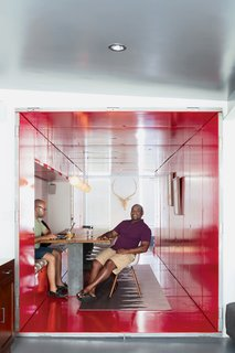"By inserting a tunnel made from 36 reclaimed commercial doors and tearing down a handful of walls, LOT-EK and contractor Andreas Scholtz brought light into the formerly unused dark hallway in Maurice Russell (right) and Jorge Fontanez's apartment. The glossy Safety Red paint by Benjamin Moore catches the light by day but ""becomes a richer, darker, very relaxing red at night,"" Fontanez says."