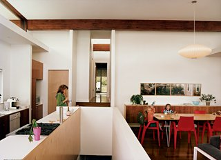 """Michele eats lunch in the kitchen; a view of the central hallway and master bedroom lays beyond. Three-year-old Maple slurps from a water bottle with Judith, five, at the dining table, also built by Jamie. The Arco armchairs are by Mario Bellino for Heller, and the Bubble lamp is by George Nelson for Herman Miller. The photograph series is by David Hilliard, titled """"That Glorious Society Called Solitude."""""""