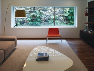 In the media room, the saturated colors of the Paper chair by Piero Lissoni for Cappellini and the Twiggy floor lamp by Foscarini contrast with the wide-screen view of the back garden.