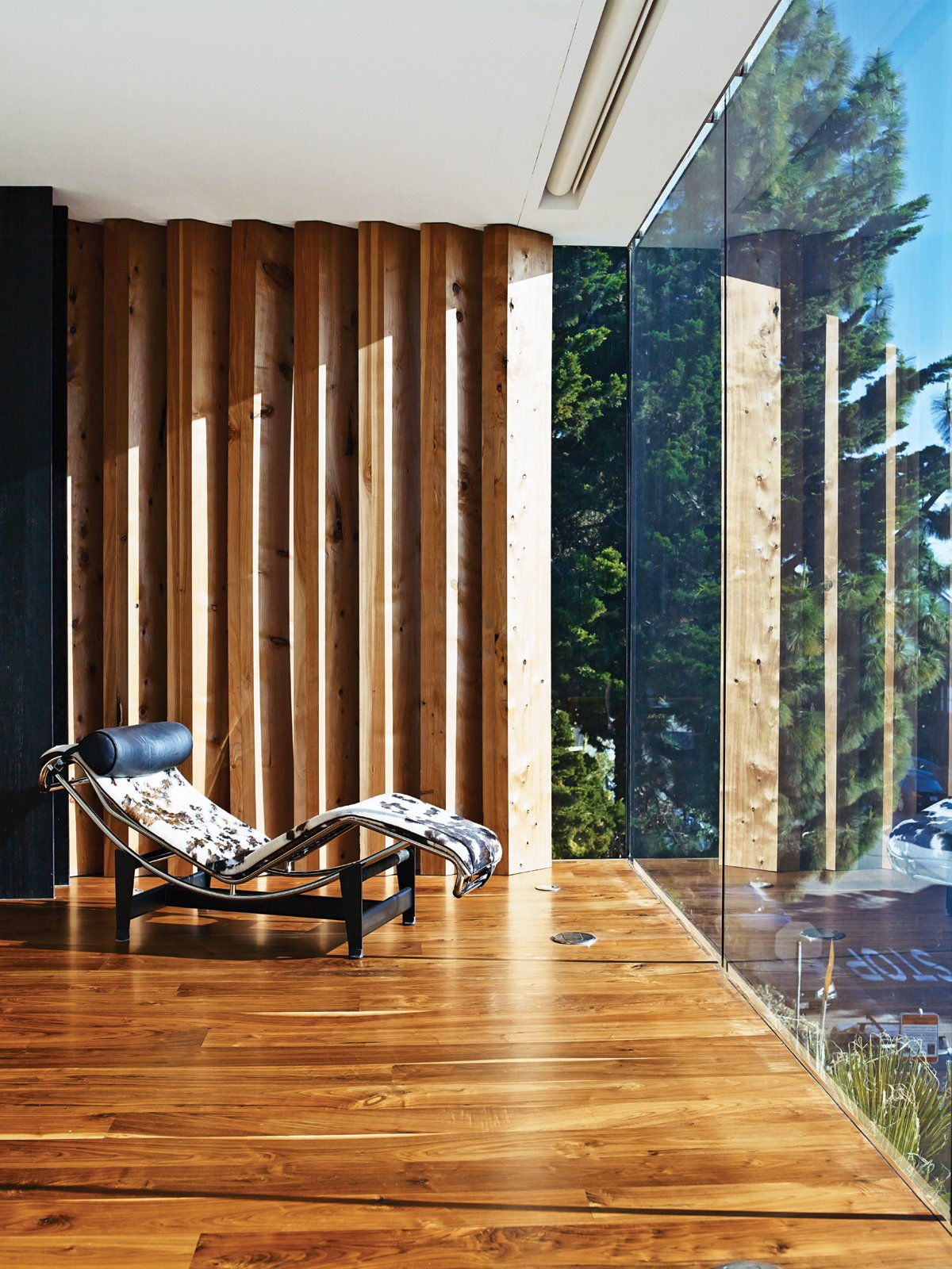 Living Room, Recliner, Medium Hardwood Floor, and Chair The master bedroom is defined on the north side by a series of indoor louvers, which allow the couple to frame and manage their views.  Photo 6 of 17 in Striking Slatted Wood and Glass Home in San Francisco