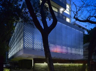 "The perforated aluminum cladding surrounds the lower-level public area, which contains the pools and gym for the tenants. Khanna and Schultz played with the idea of using stainless steel, but found that aluminum had the appropriate strength for the building's needs. ""With the lights glowing from inside, it turns the whole building into a big lantern at night,"" says Schultz."