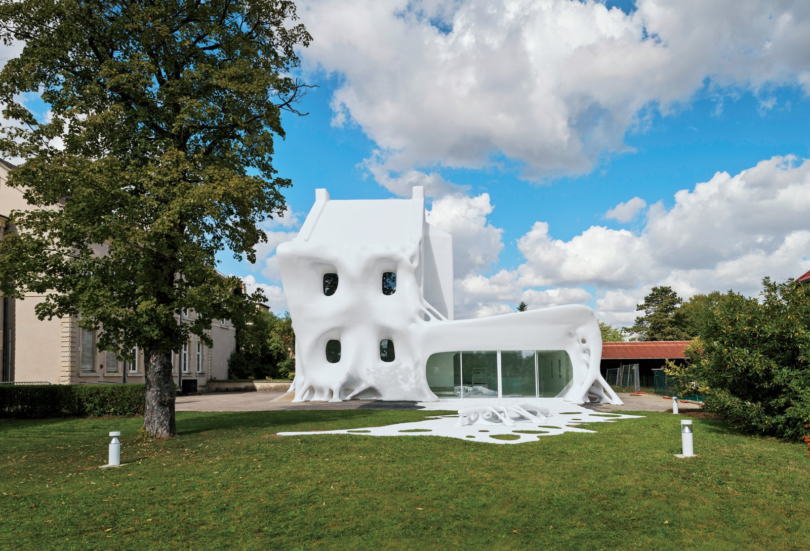 """Christophe Berdaguer and Marie Péjus named their building """"Gue(ho)st House"""" after Marcel Duchamp's aphorism """"A guest + a host = a ghost,"""" which appeared on a piece of ephemera he made in 1953. The duo translated the artist's wordplay into architect-ural form, and said: """"A house is a place where the hosts and guests share spaces. This project is like a third person, who in this context, looks like a ghost.""""  Photo 1 of 1 in Surrealist Architecture: Synagogue de Delme in France"""
