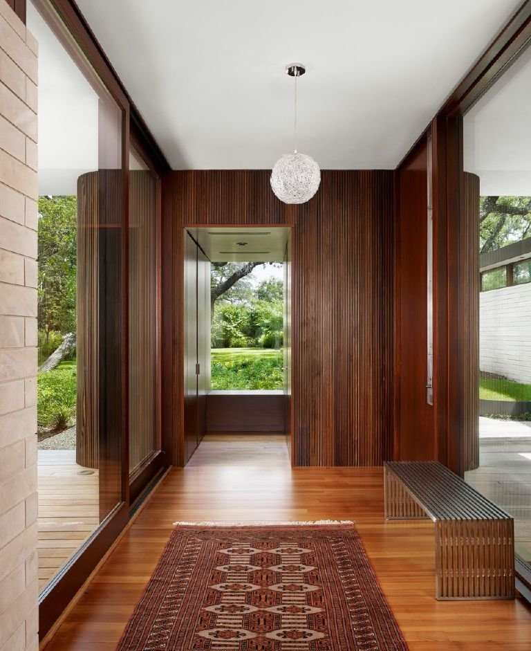 Hallway, Medium Hardwood Floor, and Rug Floor The cypress cladding carries over from the exterior to the interior of the house.  Photo 6 of 7 in A Sensitive Modern House in Austin, Texas
