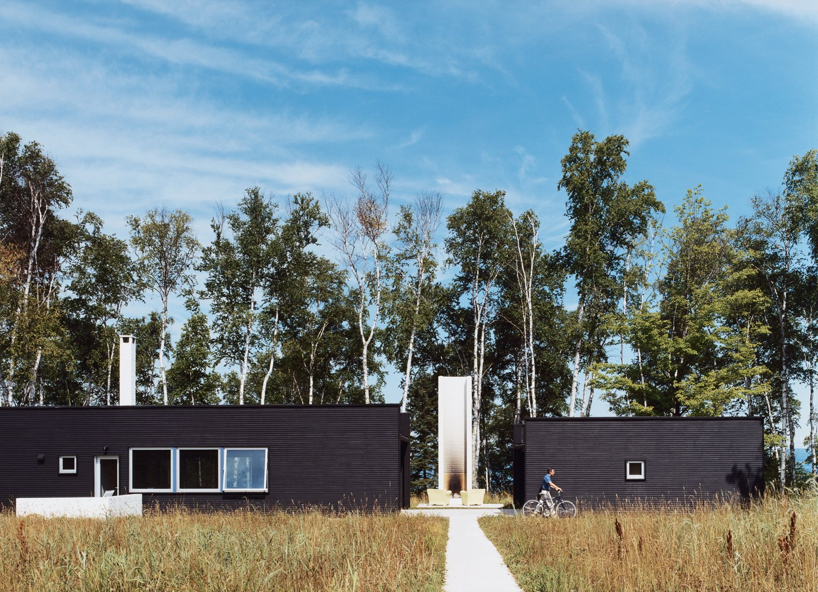Exterior, House Building Type, Flat RoofLine, and Wood Siding Material Two Black Sheds incorporates all the conventional aspects of a weekend retreat in a rather unconventional way.  Photo 4 of 15 in 15 Modern Homes with Black Exteriors from Off the Beaten Path