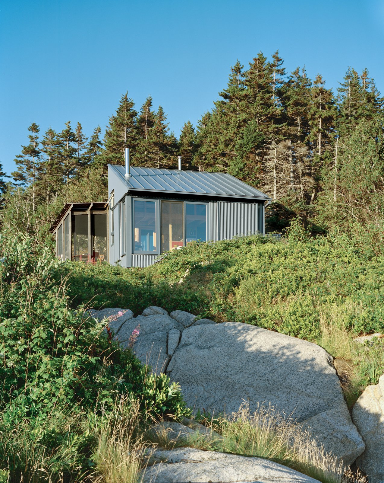 Alex devised a system that takes advantage of ocean views while protecting the cottage from that same northeasterly orientation. The large windows and doors can be shuttered with corrugated aluminum panels.  Photo 4 of 21 in A Tiny Cabin is This Writer's Off the Grid Getaway