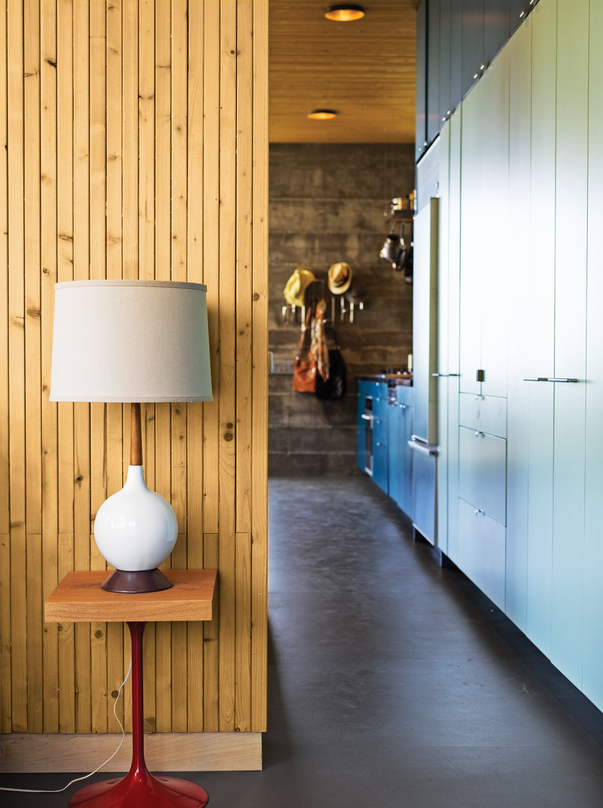 Living Room, Table Lighting, and Concrete Floor Working with a limited footprint, a daunting slope, and killer views, architect Bruce Bolander went vertical with a secluded canyon house in Malibu. A colorful, laminate-clad wall of storage stretches seamlessly from the kitchen to the bedroom, where a repurposed speaker stand serves as the bedside table. Photo by J Bennett Fitts.  Photo 1 of 9 in Malibu Canyon House with a View