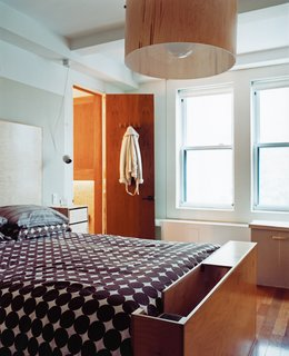 The master bedroom has a custom ramp for the dachshund at the foot of the bed and an oversize birch-veneer pendant lamp. The bedside tables are actually CD cases affixed to the wall.