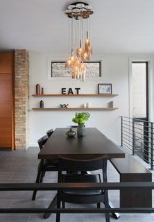 In the dining room, Fisher opted for a Cross Extension table and Profile chairs from Design Within Reach and a custom bench by JJ Woodwork. The Spillray pendants are by Axolight.