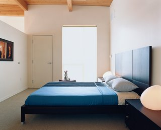 Community Building - Photo 4 of 10 - The simple, spare bedroom is brought to life by Rapaport's toy Bugs Bunny and a pair of egg-shaped Dolmen table lamps designed by Philippe Daney for Ligne Roset. The Lumeo bed is also by Ligne Roset and was designed by Peter Maly.