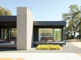 "When Abbie and Bill Burton hired Marmol Radziner to design their prefab weekend home, their two requests were ""simple-simple, replaceable materials,"" says Abbie—such as concrete floors (poured offsite in Marmol Radziner's factory) and metal panel siding—and ""the ability to be indoors or outdoors with ease."" Deep overhangs provide shade and protection from rain, so the Burtons can leave their doors open year-round and hang out on their 70-foot-long deck even in inclement weather."