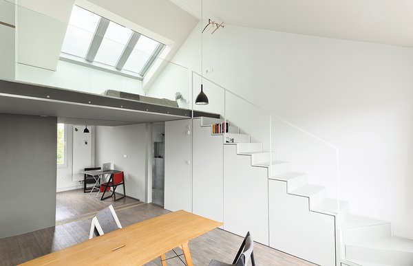 Hynam designed and built the cabinets under the stairs and a drawer that slides out from beneath the bottom step. Drink H1 pendant lamps from Rotaliana hang in the kitchen and above a Grassworks dining table by Jair Straschnow.