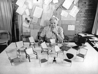 Hans J. Wegner with just a few of his famous chair designs.