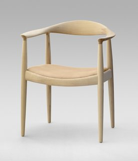 "The Round Chair from 1949 is one of Wegner's most iconic pieces and a highlight of Danish design. ""Round One"" is minimalist art reduced to its bare essentials. It required incredible craftsmanship to create such smooth curves—each of the crescent-shaped armrests are fashioned from a block of wood, and interior mortise-and-tenons hide the connection between the arms and legs. Famously, when Kennedy and Nixon sweated it out during the first televised Presidential debate, they were both sitting on Wegner's design. Manufactured by PP Møbler. Photo by Jens Mourits Sørensen."