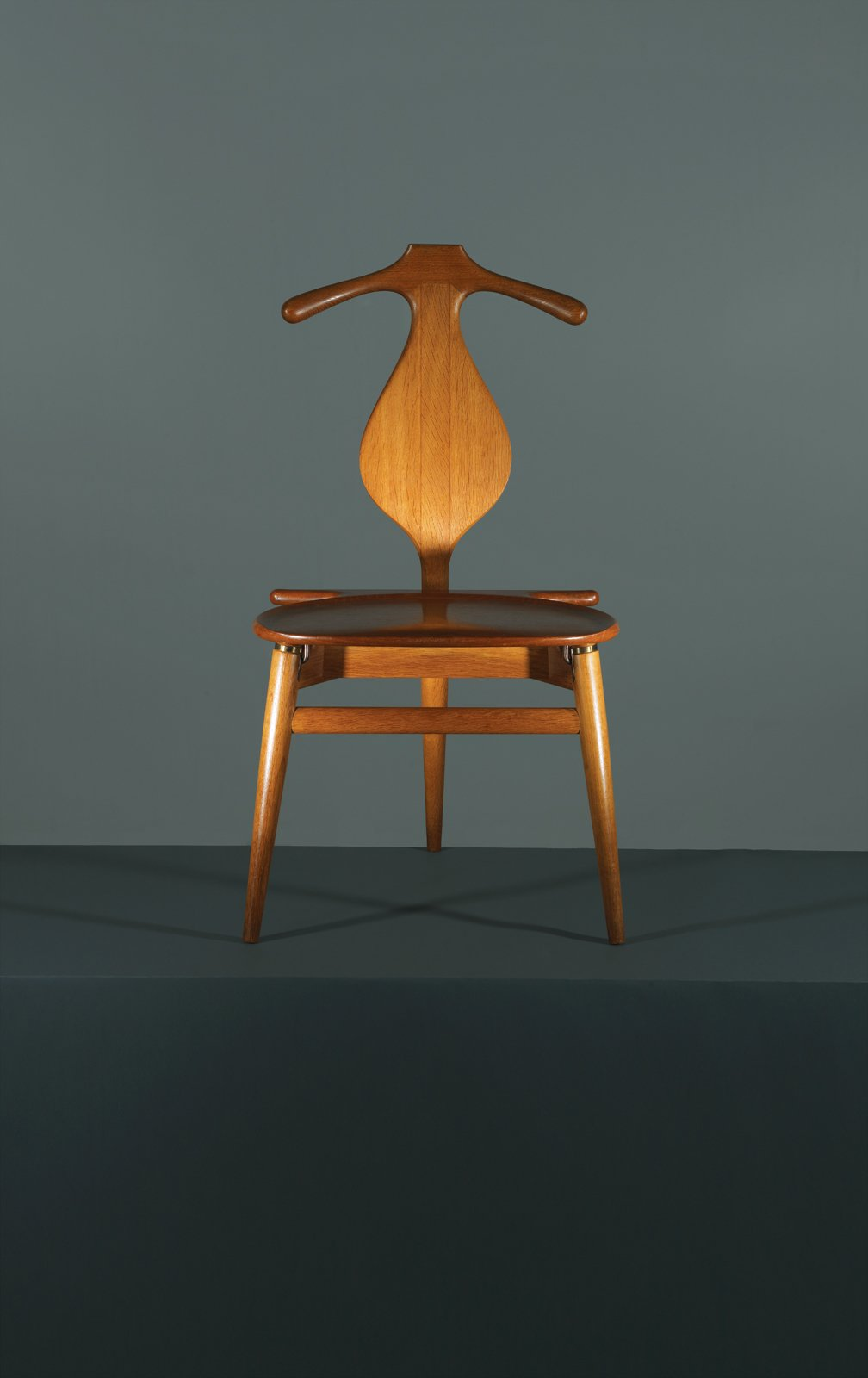 Combining the best traits of a bench and a butler, Hans Wegner's 1953 Valet chair is the one piece of midcentury-modern furniture that the fastidiously turned-out chap overlooks at his peril. Marrying formal elegance—these handsome curves have been handcrafted in PP Møbler's Danish workshop since it took over production in 1982—with a surprising functionalism, the Valet chair all but does away with the need for Jeeves. Initially a four-legged chair, Wegner decided to trim the final product and arrived at a tripod design, though he maintained the initial design when Danish King Frederick IX requested his own. Manufactured by PP Møbler.  Photo 5 of 9 in 8 Iconic Chairs by Hans Wegner from This Way, Gentlemen