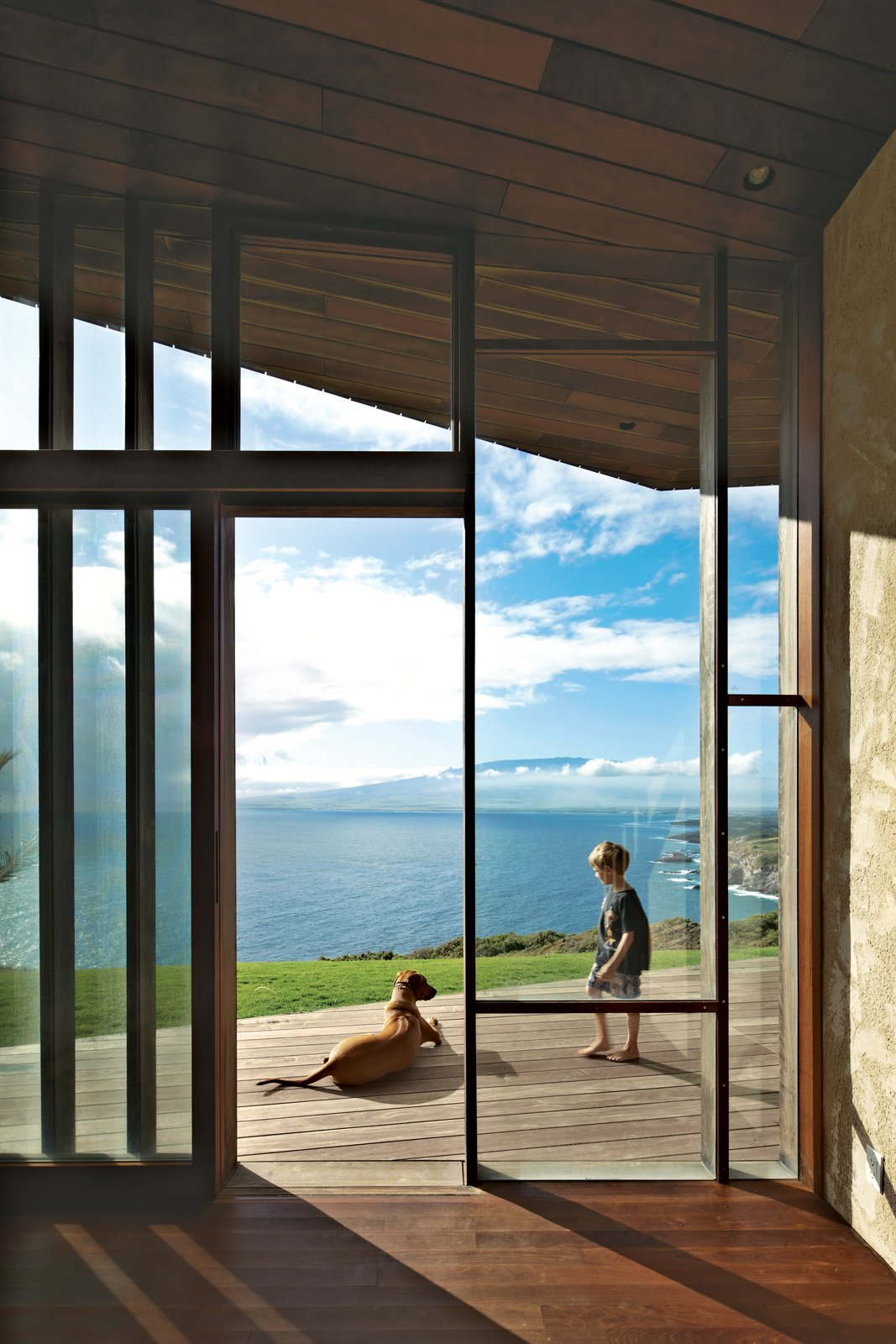 Miha hangs out with Kea, the dog, on the wooden deck that extends the living space outdoors. Tagged: Outdoor, Large Patio, Porch, Deck, and Wood Patio, Porch, Deck.  Photo 5 of 10 in Clifftop House with Angled Roof in Maui