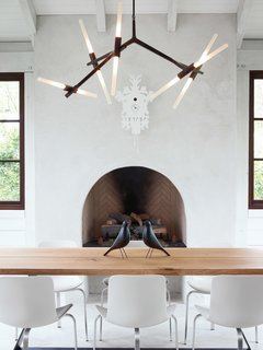 The home's informal dining space has a slightly rustic feel, sporting bronze and wood in the form of a Lindsey Adams Adelman chandelier for Roll & Hill and a table by Terry Dwan, mixed with folk-art touches like the Eames House Birds and a cuckoo clock from Diamantini & Domeniconi. The PK8 chairs from Republic of Fritz Hansen were designed by Poul Kjærlholm and sourced from Kuhl-Linscomb in Houston, Texas.