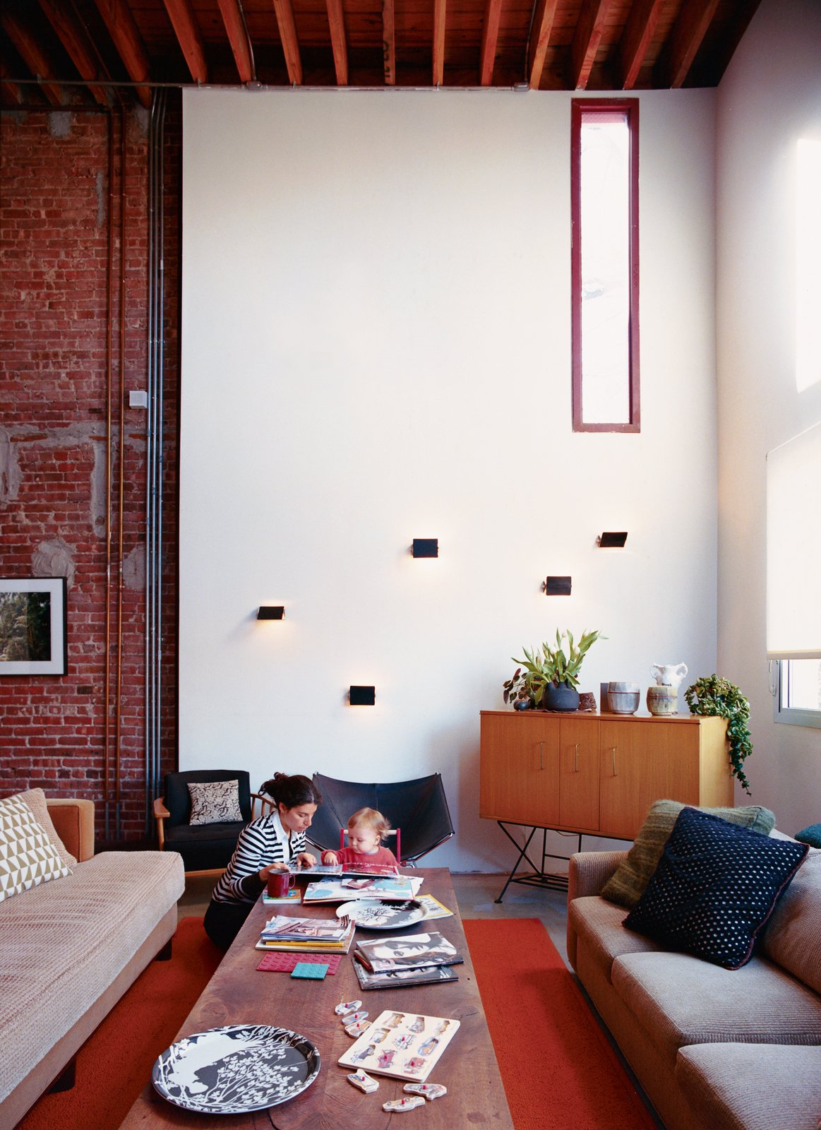 Living Room, Rug Floor, Sofa, Coffee Tables, Wall Lighting, Chair, and Storage Darcy Miro and her son, Lucien, enjoy a moment in their new double-height living room. The Charlotte Perriand wall sconces are vintage finds.  Photo 1 of 5 in A House Grows in Brooklyn
