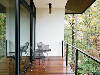 Wire chairs by Rejuvenation and pendants by Hinkley Lighting grace the balcony outside.