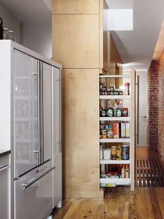 The sliding pantry cabinet doubles as a room divider when fully extended, separating the kitchen from the bedrooms.
