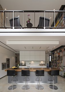The kitchen, Bulthaup island, and overhanging entrance-level comprise the remainder of the extension. A five-story double-sided, weld-free aluminum bookcase begins in the kitchen and rises through the lounge. A staircase traces every inch of it so that material can be readily accessed.