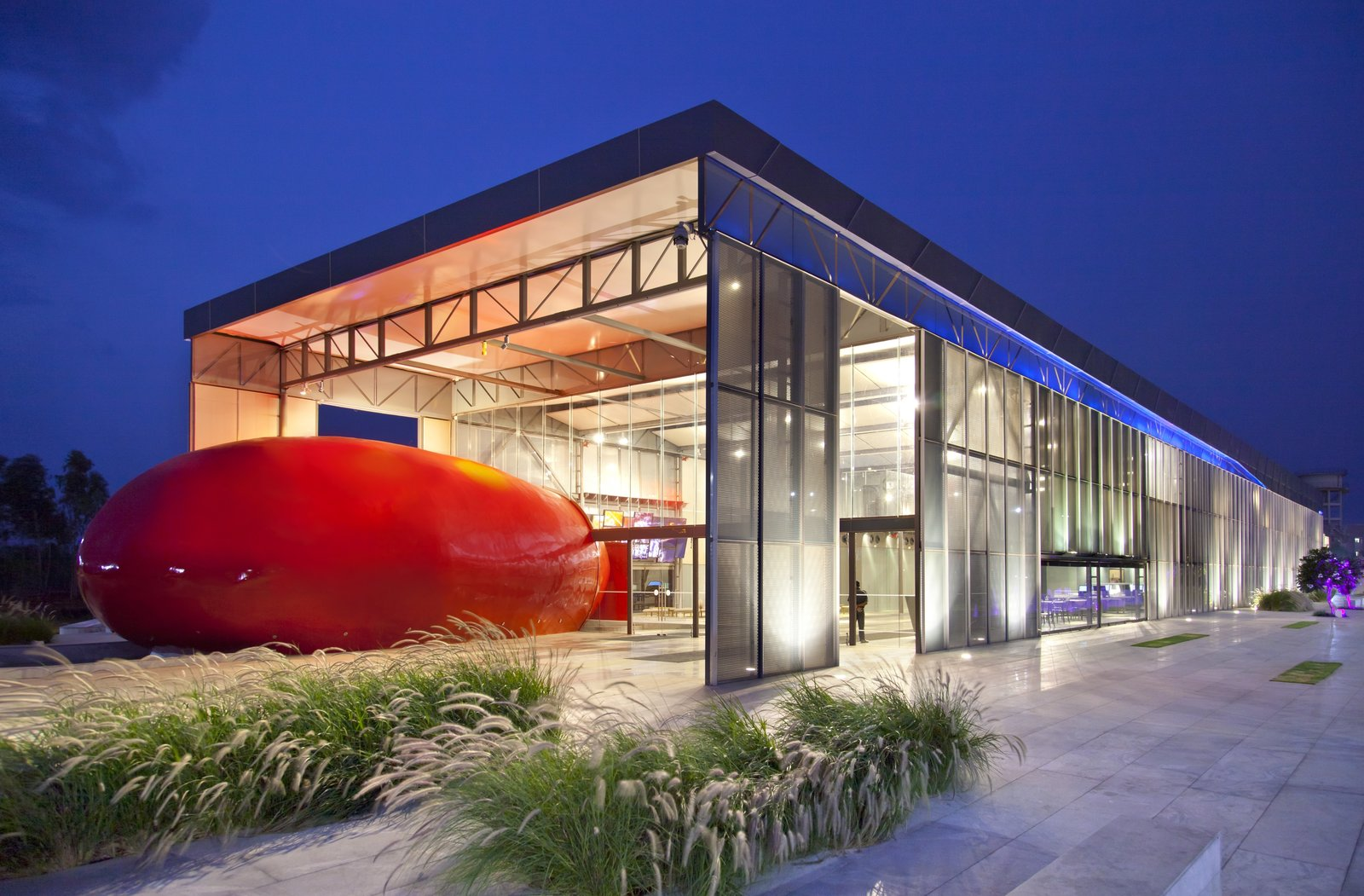 The building wraps around a red core—the auditorium—covered in glass fiber.  Photo 1 of 7 in A Modern Town Hall in Bangalore