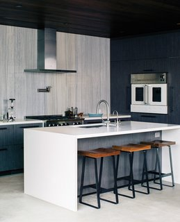 In this sleek kitchen, the range and wall oven are by BlueStar, the hood is from Zephyr, and the island is Caesarstone.