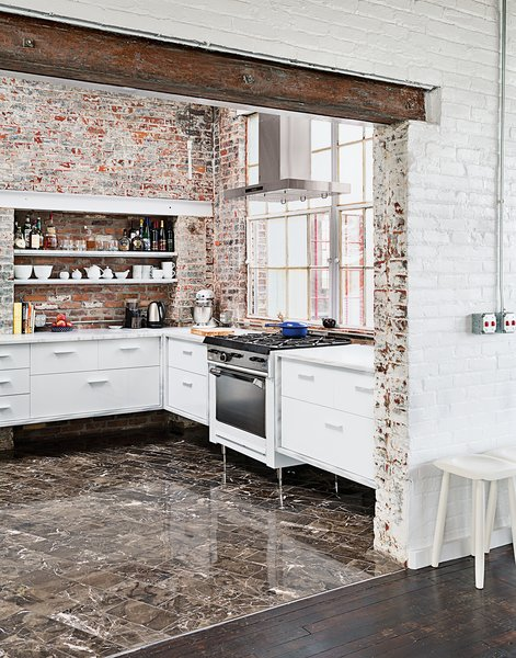 Among the couple's cost-saving measures was outfitting the kitchen with their own custom cabinetry. The brick and windows are original, the Garland stove was a Craigslist find, and the floor tile was found on closeout at a cost of about $1 per square foot.