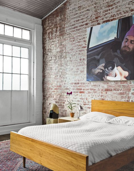 In the guest bedroom, a painting by Monique Crine hangs on the original brick wall above a Miles & May bed and side table. The rug is from ABC Carpet & Home.  Photo 6 of 7 in A Design Duo Takes Over A Whole Factory
